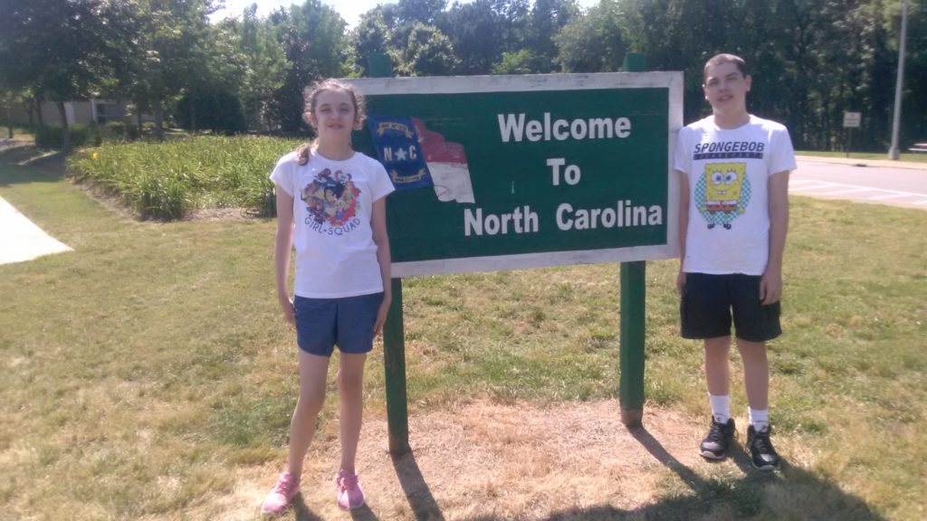 kids in front of welcome to north carolina sign